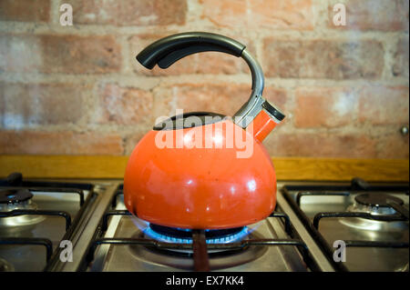 Retro orange kettle on stainless steel gas stove against a rustic industrial brick wall. - Stock Photo