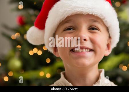 Smiling boy (6-7) wearing Santa hat - Stock Photo
