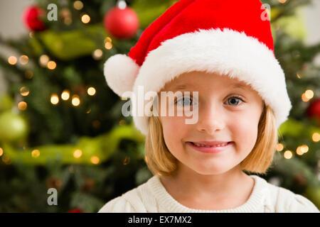 Smiling girl (6-7) wearing Santa hat - Stock Photo
