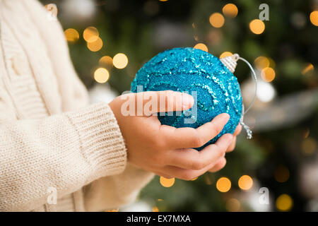 Hands of boy (6-7) holding blue bauble - Stock Photo
