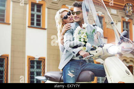 Attractive couple on the retro motorbike - Stock Photo