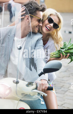 Adorable lady sitting on the scooter with her boyfriend - Stock Photo