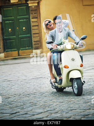 Handsome guy riding a scooter with his girlfriend - Stock Photo