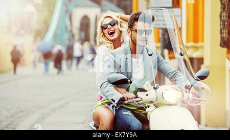 Handsome man riding a scooter with laughing woman - Stock Photo