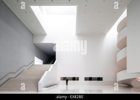 Overall view of grand foyer with single person. Szczecin Philharmonic Hall, Szczecin, Poland. Architect: Estudio - Stock Photo