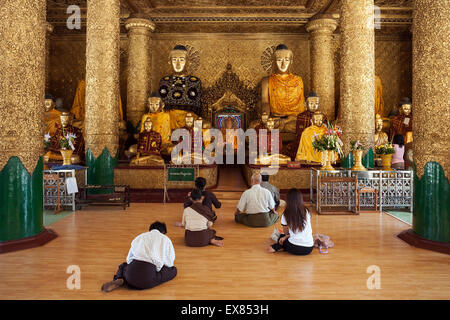 People meditating in front of Buddha statues, Shwedagon Pagoda, Yangon, Myanmar - Stock Photo