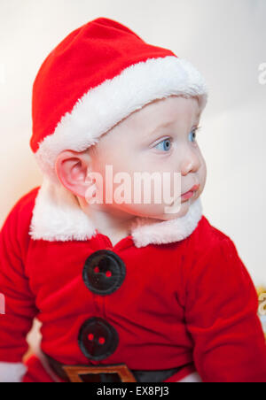 Cute baby in father Christmas outfit - Stock Photo