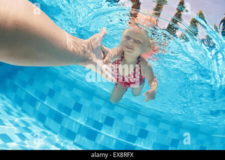 Joyful baby girl diving underwater with fun and holding parents hand for assistance in outdoor tropical swimming - Stock Photo
