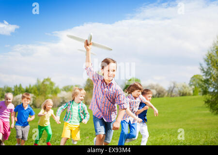 Cute boy and his friends run with big airplane toy - Stock Photo