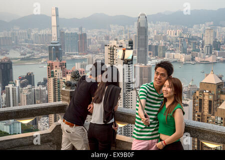 Young asian couple using a selfie stick in front of Hong Kong Skyline, from Victoria peak - Stock Photo