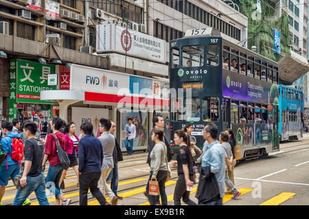 Commuters Crossing Busy Hong Kong Street, with a tram in the background - Stock Photo