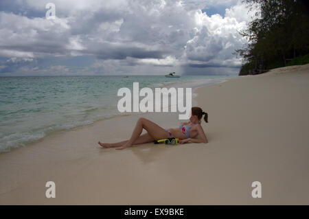 young woman lying on the sandy shores of the Indian Ocean, Denis island, Seychelles - Stock Photo