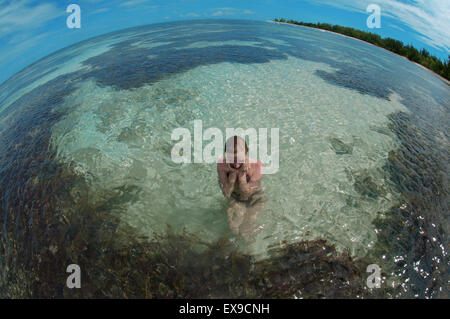 A young woman sits in water, Denis island, Indian Ocean, Seychelles - Stock Photo