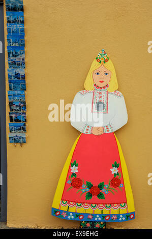 Postcard rack next to a traditionally dressed woman shop sign. Old town. Tallinn. Estonia - Stock Photo