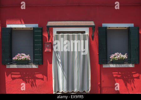 A window display outside one of the beautifully coloured house in Burano, Venice - Stock Photo
