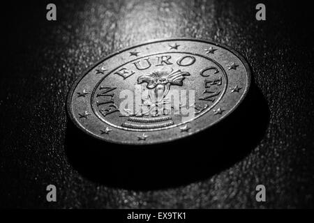 A one cent euro coin on a wooden surface, black and white, dark atmosphere, close up detailed view, concept of crisis - Stock Photo