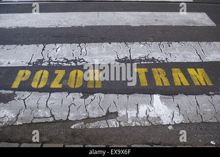 A 'beware of tram' warning sign painted on the tarmac at a pedestrian crossing. - Stock Photo