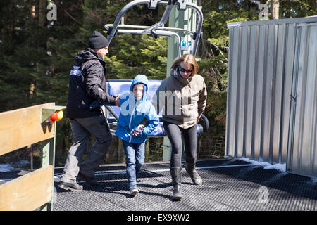 Mother and Child receiving help to get off a ski chair lift - Stock Photo
