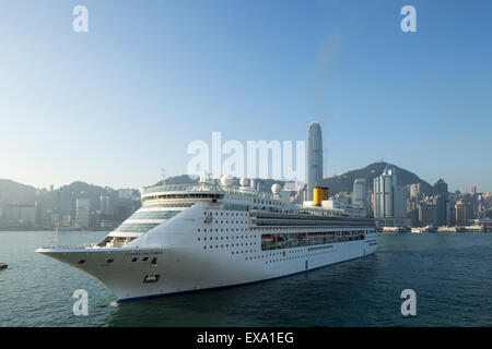 China, Hong Kong, Cruise ship Costa Victoria motors into Hong Kong Harbour with IFC2 and city skyline at sunrise - Stock Photo