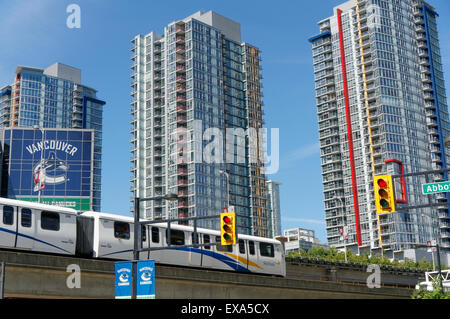 SkyTrain elevated train with newly built condominium towers in the background, Vancouver, BC, Canada - Stock Photo