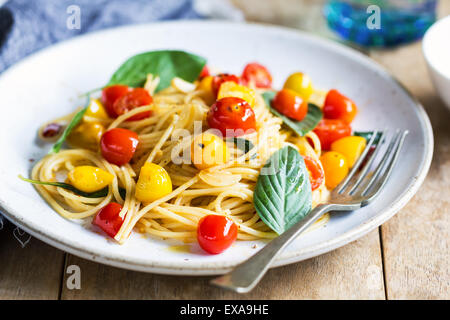 Spaghetti with red and yellow cherry tomato by sea salt - Stock Photo