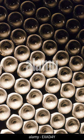 Dusty wine bottles stacked up in the wine museum at the Sandeman Winery. - Stock Photo