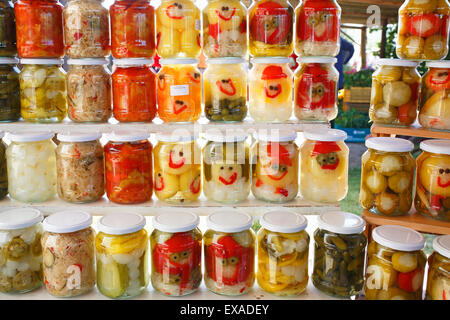 Pickled peppers, cucumbers, onions and other vegetables in glasses with funny faces, farmers' market on Lake Balaton, Hungary