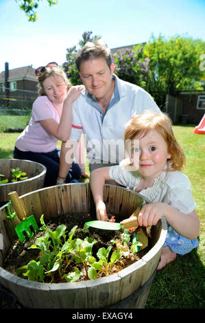 A family with young daughter planting seeds in their back garden, Gloucestershire UK - Stock Photo