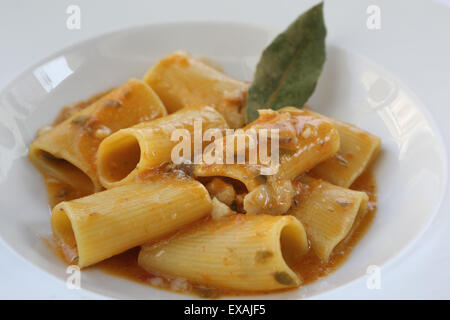 Tubes of southern Italian paccheri pasta served with a tomato sauce and pieces of scorpion fish in Monopoli, Apulia, - Stock Photo