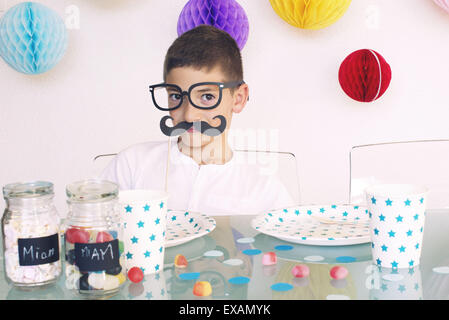 Boy wearing fake glasses and mustache at a birthday party - Stock Photo