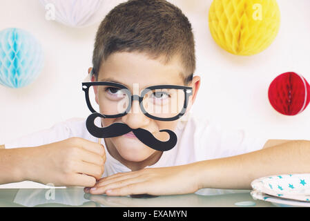 Boy wearing fake glasses and mustache at a birthday party, portrait - Stock Photo