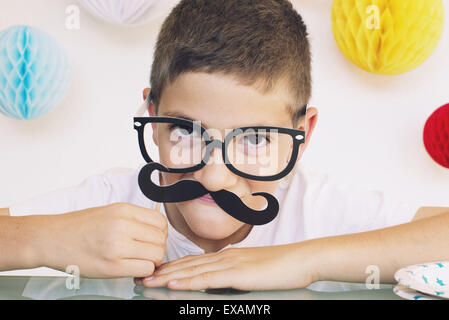 Boy wearing fake mustache and glasses at a birthday party - Stock Photo