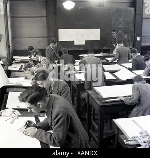 1950s, young male engineering apprentices in classroom doing technical drawing. - Stock Photo