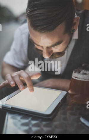 handsome big moustache hipster man using tablet sitting at the bar - Stock Photo