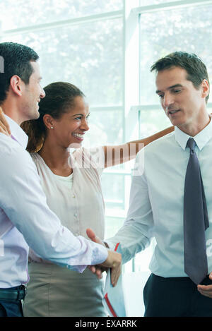 Business team members congratulating each other - Stock Photo