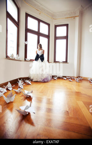 Bride stands in an empty flat in an old building, looks from the window - Stock Photo