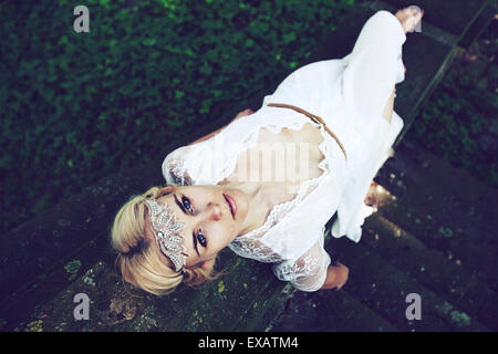 young woman lies in white top dress on stairs in the wood - Stock Photo