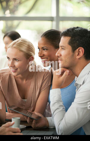 Colleagues listening attentively to story during coffee break - Stock Photo