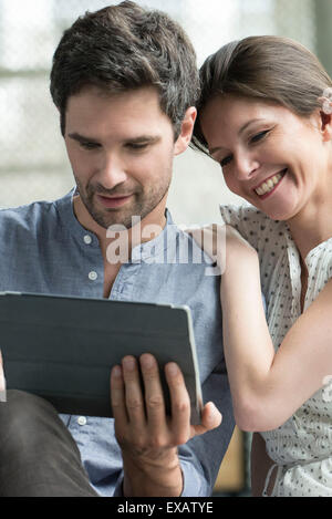 Couple using digital tablet together at home - Stock Photo