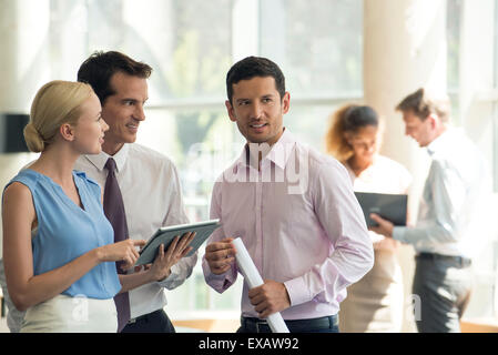 Professionals collaborating using digital tablet - Stock Photo