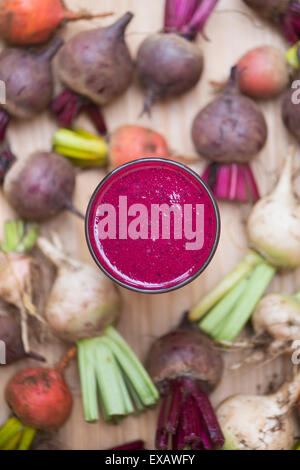Beta vulgaris. Beetroot smoothie drink surrounded by harvested red, yellow and white beetroots - Stock Photo