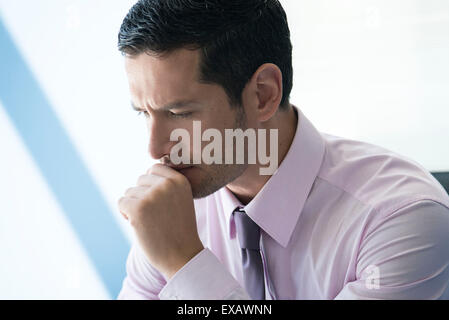 Businessman with hand under chin with look of concern - Stock Photo