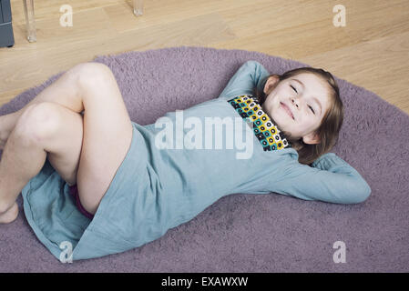 Girl lying on floor with hands behind head, smiling - Stock Photo