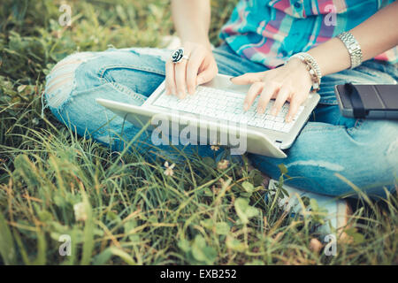 close up hands beautiful young hipster woman using laptop and tablet in the park - Stock Photo