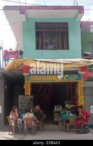 tourists sitting in the shade outside Sunshine Cafe in Manali, in the Indian state of Himachal Pradesh - Stock Photo