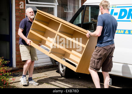 Father helping son to move furniture out of a house carrying a chest of drawers in to a self-drive hired removal - Stock Photo