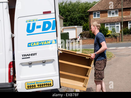 A man putting a chest of drawers furniture in to a self-drive hired removal van for house removals. Surrey, England, - Stock Photo