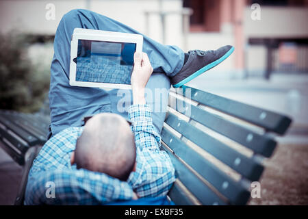 handsome hipster casual multitasking modern man using tablet in the city - Stock Photo