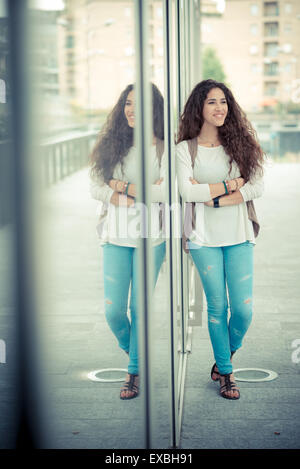 beautiful curly long brunette hair moroccan woman in the city - Stock Photo