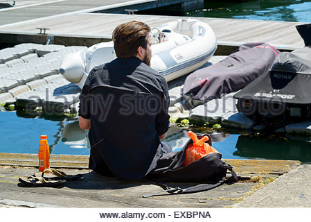 Young man having lunch on quayside, Poole, Dorset England UK - Stock Photo
